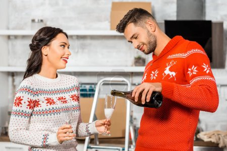 handsome smiling man pouring champagne into glass in girlfriend hand in kitchen at new home