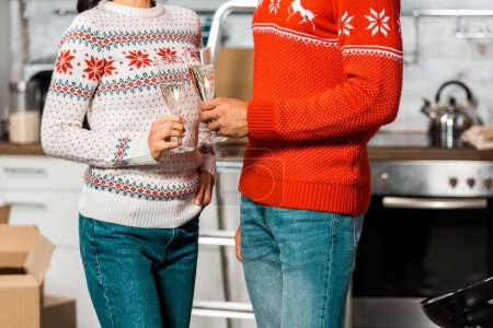 Photo for Cropped image of couple clinking by champagne glasses for celebration relocation - Royalty Free Image