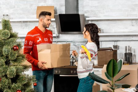 handsome young man holding cardboard box with baubles for decorating christmas tree while his girlfriend standing near in kitchen at home