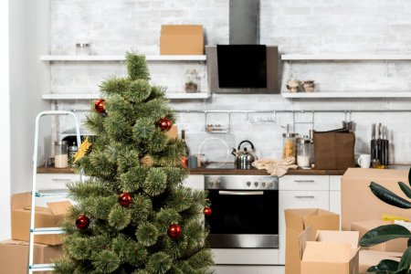 interior of kitchen with decorated christmas tree and cardboard boxes during relocation at new home