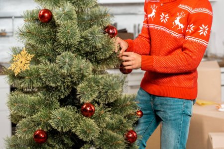 Photo for Cropped image of man decorating christmas tree by baubles in kitchen at home - Royalty Free Image