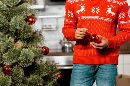 cropped image of man decorating christmas tree by baubles at home