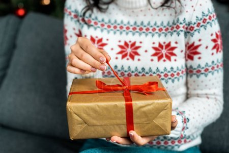 partial view of woman untying christmas present box on sofa at home