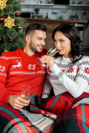 selective focus of couple ceebrating with champagne glasses on sofa near christmas tree at home