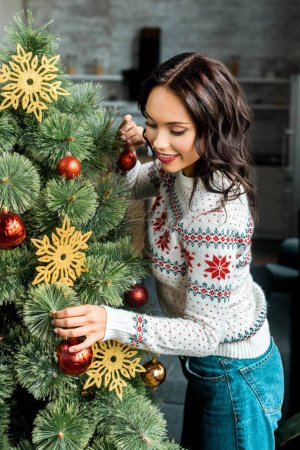 happy young woman decorating christmas tree by baubles at home