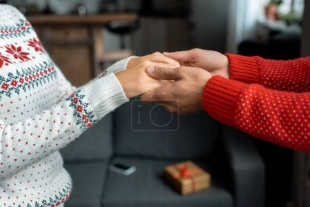 cropped image of man holding hands and leading girlfriend for making surprise on christmas at home