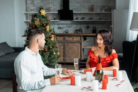 Photo pour Couple de célébrer Noël avec des verres de champagne à table servi avec des bougies à la maison - image libre de droit