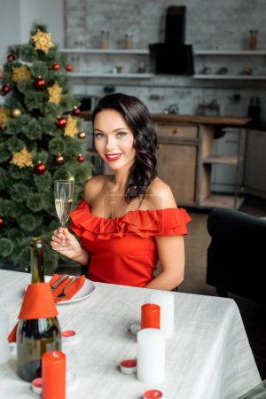 attractive young woman with champagne glass sitting at served table with candles on christmas at home
