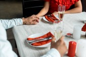 cropped image of couple holding hands and celebrating christmas with champagne glasses at served table with candles at home