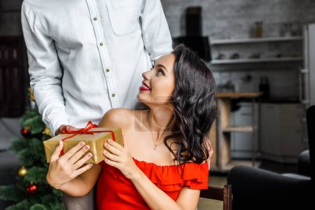 cropped image of man gifting christmas present to girlfriend at home