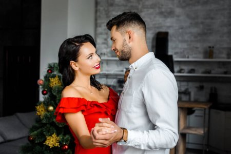 side view of happy young couple looking at each other and dancing on christmas at home