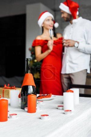 Photo pour Mise au point sélective de bouteille de champagne avec bougies servi table de Noël et de couple pour célébrer avec des verres de champagne derrière à la maison - image libre de droit