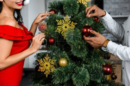 Photo for Cropped image of couple decorating christmas tree by baubles at home - Royalty Free Image