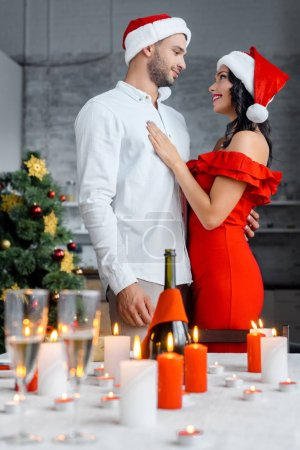 couple in christmas hats embracing each other near served table with champagne glasses and candles at home
