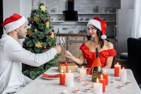 Photo pour Heureux couple en chapeaux de Noël fête et cliquetis de verres de champagne près de table servi avec des bougies à la maison - image libre de droit