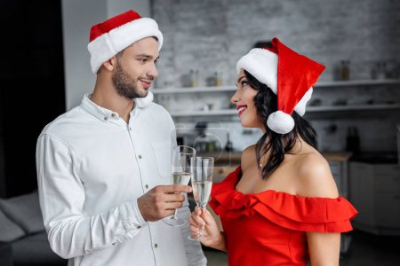 young couple in christmas hats celebrating and clinking by champagne glasses at home