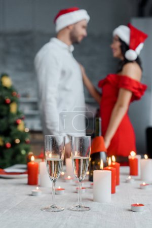 selective focus of champagne glasses at served table with candles and couple in christmas hats standing behind at home