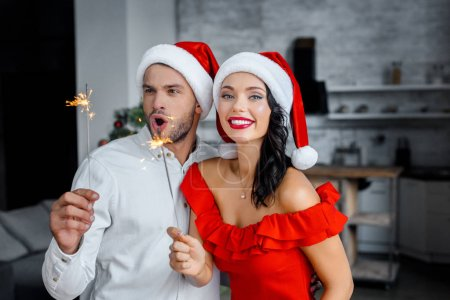 emotional happy couple in christmas hats celebrating with sparkles at home