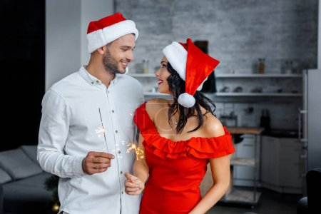 happy young couple in christmas hats with sparkles looking at each other at home