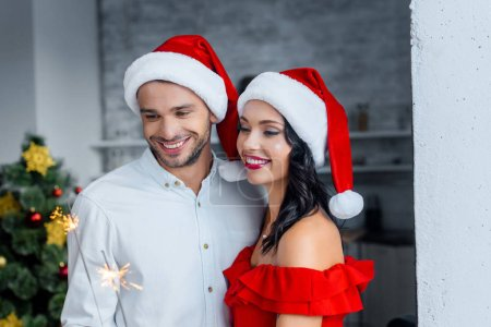 cheerful young couple in christmas hats celebrating with sparkles at home