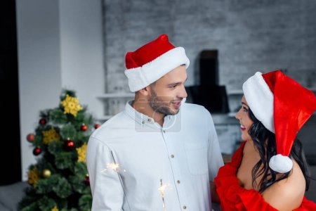 smiling young couple in christmas hats holding bengal lights and looking at each other at home
