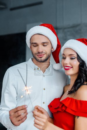 selective focus of young couple in christmas hats celebrating with bengal lights at home