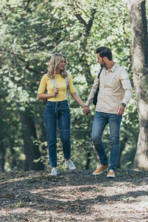 young couple holding hands while walking in autumn park together