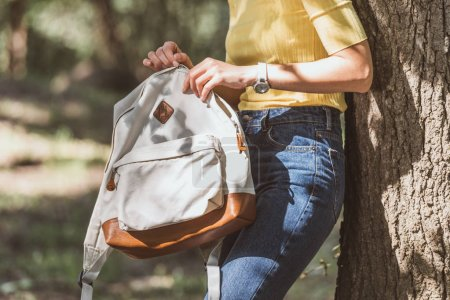 partial view of woman with backpack leaning on tree in park