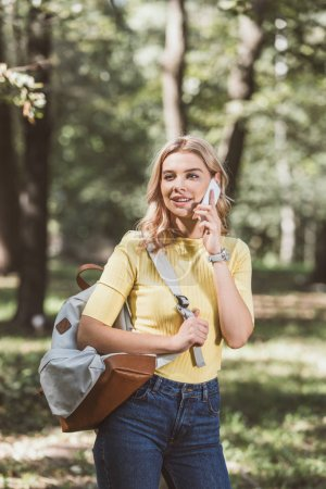 portrait of young woman with backpack talking on smartphone in park