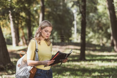 Photo for Portrait of young tourist with backpack and map in park - Royalty Free Image