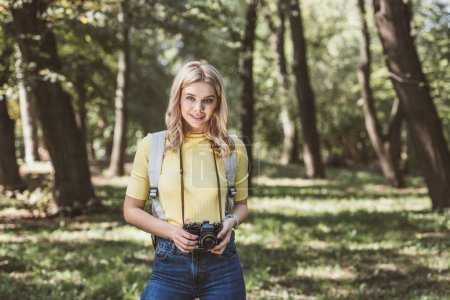 portrait of young tourist with photo camera and backpack in park
