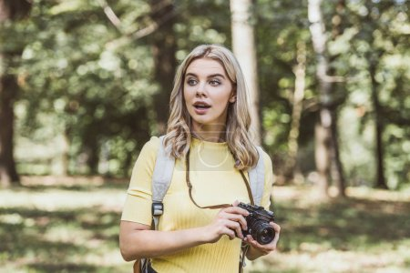 Portrait de jeune touriste émotionnelle avec photo caméra regardant loin dans le parc