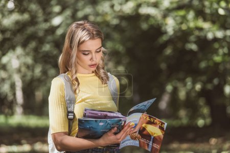 portrait of focused young woman reading magazine in park