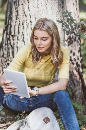 portrait of young woman using digital tablet while resting in park