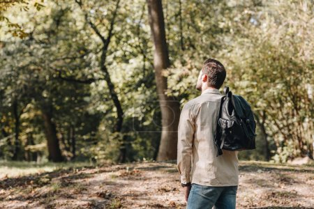 back view of stylish young man with backpack in autumn park