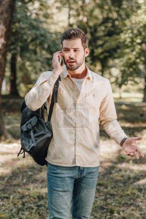 Photo pour Portrait d'homme avec sac à dos parler sur smartphone dans le parc - image libre de droit
