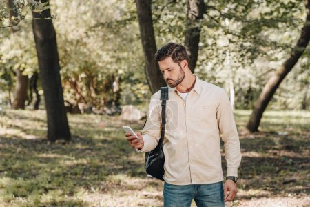 stylish man in casual clothing with backpack using smartphone in park