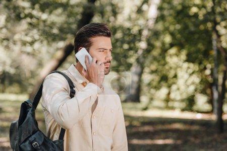 Photo pour Vue de côté du jeune homme avec sac à dos parler sur smartphone dans le parc - image libre de droit