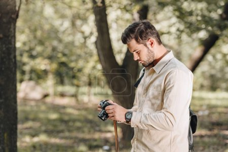 side view of tourist with photo camera in hands in autumn park