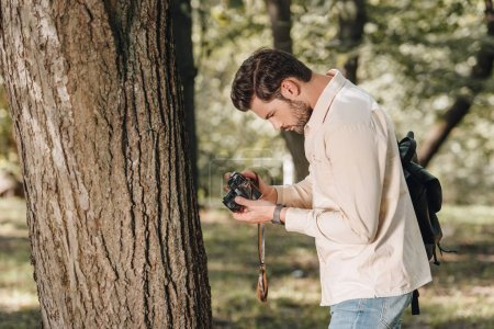 side view of young traveler with photo camera in park