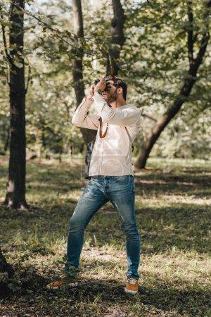 Foto de Foto de joven turista toma en cámara de fotos en el Parque otoño - Imagen libre de derechos