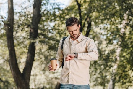 portrait of man with backpack and coffee to go checking time in park