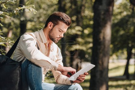 Photo for Side view of man using digital tablet in park - Royalty Free Image
