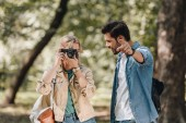 portrait of couple of young travelers with photo camera taking picture in park