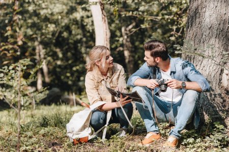Photo for Couple of travelers with map and photo camera resting in park - Royalty Free Image