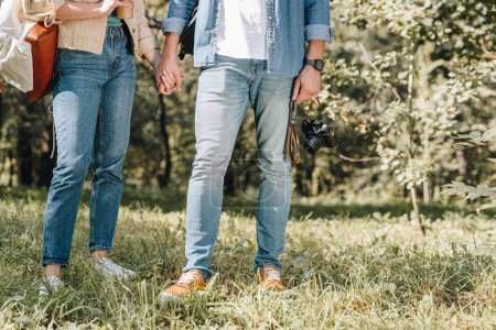 cropped shot of couple holding hands in park