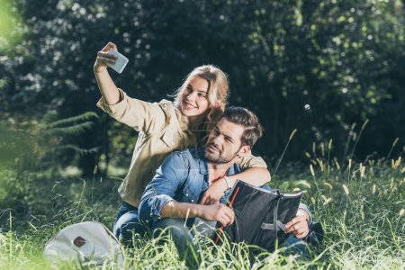 smiling tourists with map taking selfie on smartphone in park