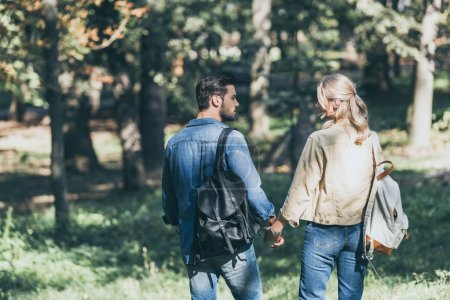 Photo for Back view of young couple with backpacks walking in autumn park - Royalty Free Image