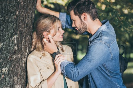 romantic couple looking at each other in autumn park