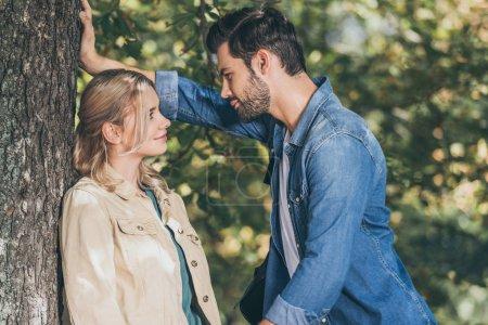 Photo pour Vue latérale du jeune couple romantique, regardant l'autre dans le parc automne - image libre de droit